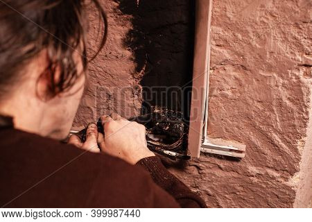 A Man Fixes A Burnt Socket. Short Circuit, Burnt Wires. Traces Of Smoke And Fire On The Wall. The El