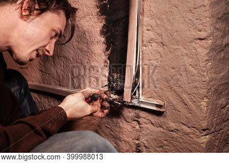 A Man Fixes A Burnt Socket. Short Circuit, Burnt Wires. Traces Of Smoke Fire On The Wall. The Electr
