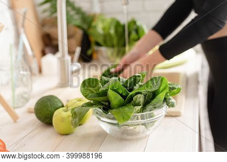 Woman Washing Celery In The Kitchen Sink