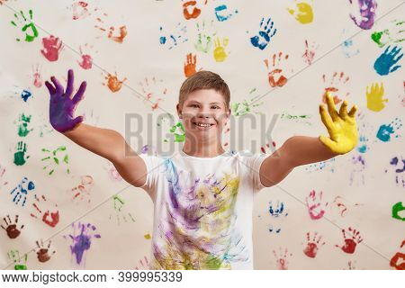 Happy Disabled Boy With Down Syndrome Smiling At Camera While Reaching Out His Hands Painted In Colo