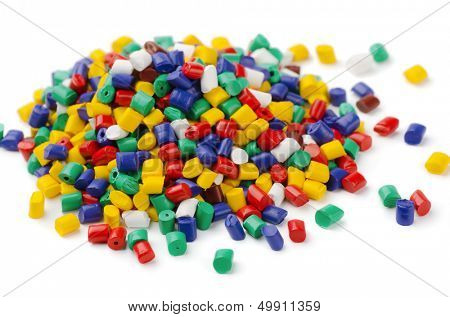 Pile of colorful plastic polymer granules isolated on white