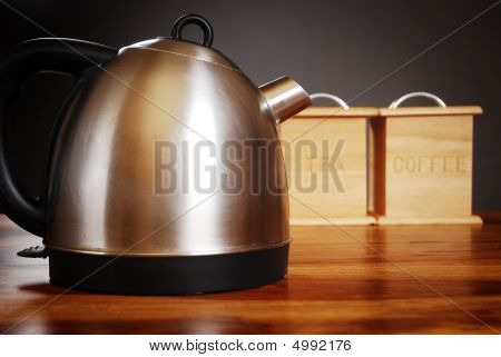 Kettle And Mug On Dark Background With Tea And Coffee Cannisters