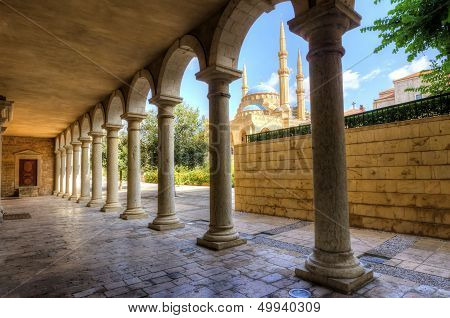 The Mohammad Al-Amin Mosque situated in Downtown Beirut in Lebanon as viewed through the pillars of the Greek Orthodox church of St George. poster