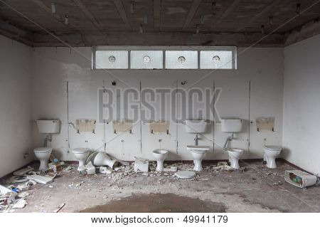 A row of partially destroyed toilets in a building under demolition