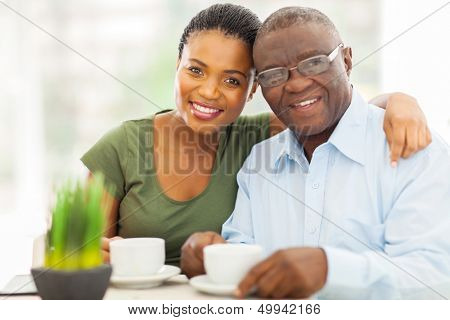 beautiful young adult african girl and father having coffee at home poster