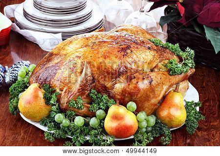 Thanksgiving or Christmas turkey dinner with fresh pears grapes and parsley. Poinsettia flower arrangement dishes and wine glasses in background. poster