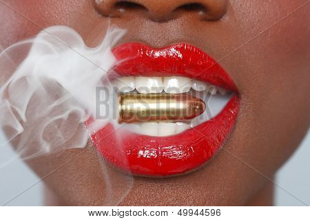 Close up of a woman with red lips biting a bullet