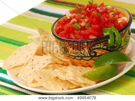Freshly made tortilla chips with a corn and tomato salsa with limes poster