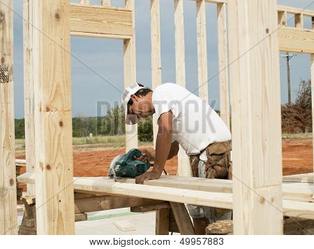 Framer Sawing Piece Of Lumber