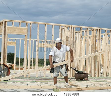 Framer Moving Large Piece Of Lumber