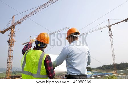 Site Manager And Construction Worker Checking Plans