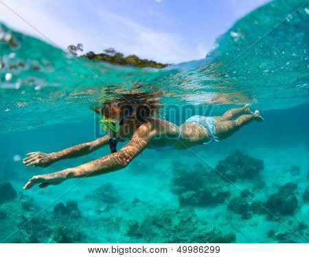 Young lady snorkeling in a clear tropical sea