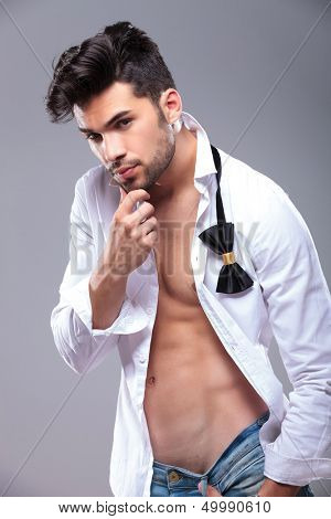 sexy casual young man with unbuttoned shirt touching his chin and looking at the camera. on gray background