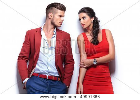 casual fashion man and woman looking at each other while leaning against white wall