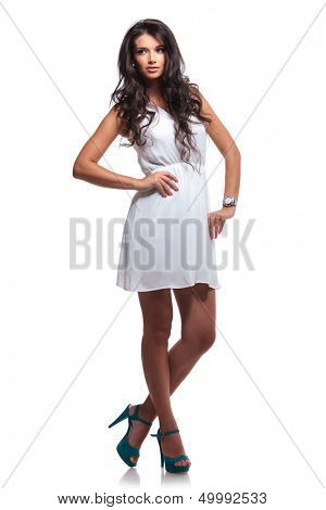 full length picture of a young beautiful woman looking away while holding her hands on her hips. isolated on a white background