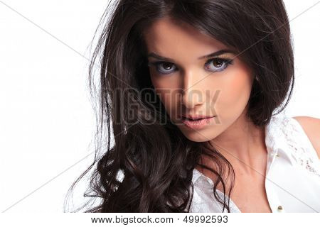 closeup of a young beautiful woman looking into the camera with a serious look. isolated on a white background
