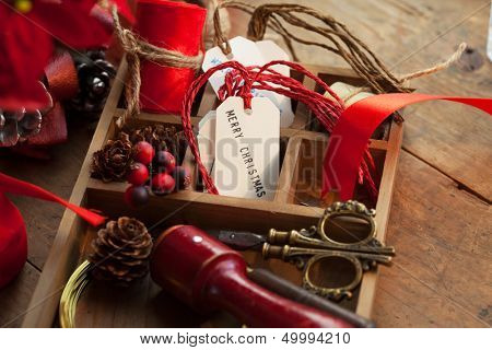 Christmas preparation. Tray with ribbons and christmas tags, on an old wooden table with vintage feel.