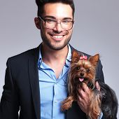 casual young man holding a puppy and looking at the camera with a smile on his face. on gray background poster