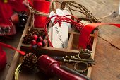 Christmas preparation. Tray with ribbons and christmas tags, on an old wooden table with vintage feel.  poster