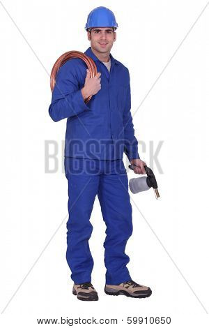 Man holding copper piping and blowtorch