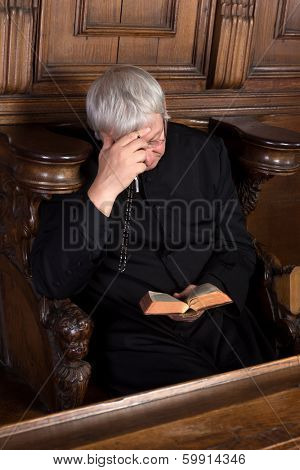 Vintage priest dressed in black cassock reading and holding a rosary