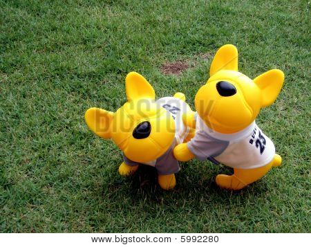 Yellow Rubber Toy Dogs Playing On The Grass poster