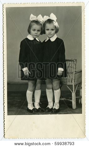 MOSCOW, USSR - CIRCA 1960: An antique photo shows studio portrait of a two little sisters.