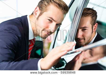 Seller or car salesman in car dealership presenting the reflecting car paint of his new and used cars in the showroom