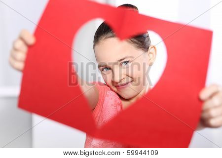Child cut from red paper heart