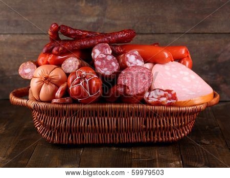 Lot of different sausages in basket on wooden table on wooden background poster