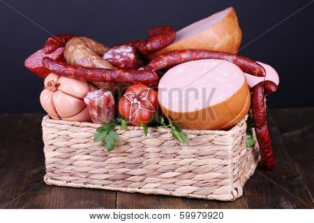 Lot of different sausages in basket on wooden table on black background poster