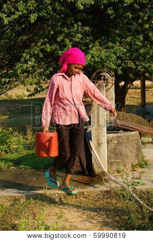 People  Scoop Water From Water Well