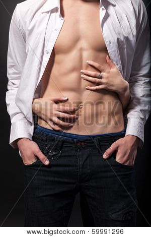 Woman's hands on a sexy man's torso on a black background poster