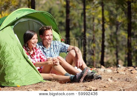 Camping couple in tent sitting looking at view in forest. Campers smiling happy outdoors in forest. Happy multiracial couple having fun relaxing after outdoor activity. Asian woman, Caucasian man.