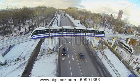 Monorail train passes over a four-lane road in the city, aerial view
