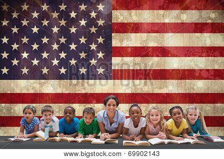 Cute pupils smiling at camera with teacher against usa flag in grunge effect poster