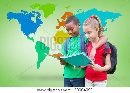 Cute pupils reading against green vignette with world map poster
