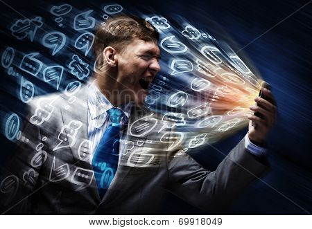 Aggressive businessman screaming fiercely in mobile phone