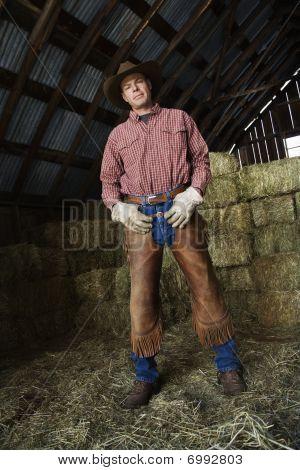 Man In A Barn Wearing A Cowboy Hat