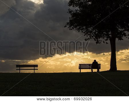 Silhouette man alone on a bench during a cloudy sunny sunset