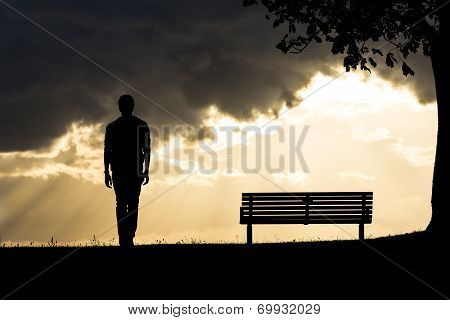 Portrait of a silhouette man walking away from a bench at sunset