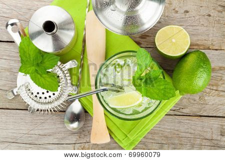 Fresh mojito cocktail and bar utensils on wooden table