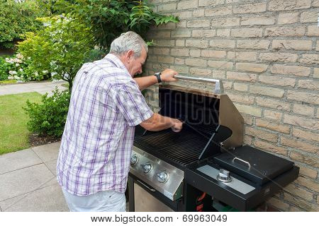 Senior Man Cleaning Barbecue