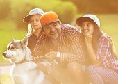 Dad and his two daughters in park with dog Husky spend fun time. poster