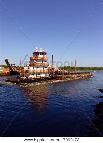Tugboat pushing barge up river