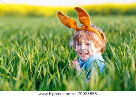 Cute Little Kid Boy With Easter Bunny Ears  In Green Grass