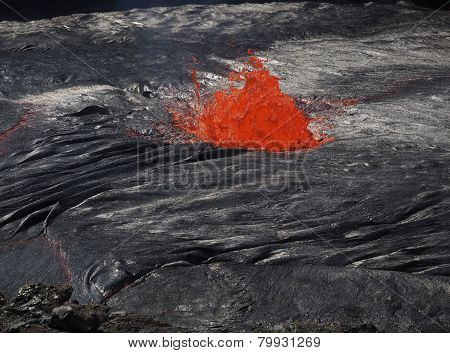 Lava burst inside the Erta Ale volcano. This lava lake is continuously flowing and bubbling inside this 60m-large crater. Located in Ethiopia close to the border with Erithrea. poster