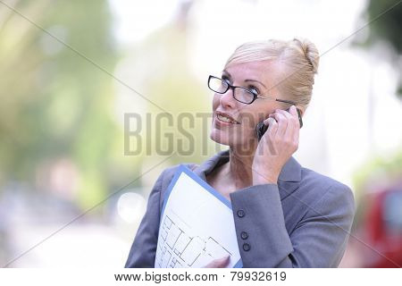 Mature female real estate agent talking on phone with copyspace