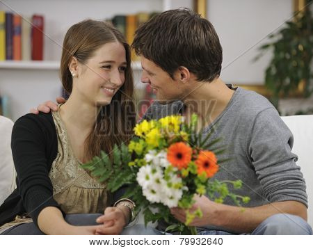 Romantic valentines gift: Boyfriend giving bunch of flowers to his girlfriend