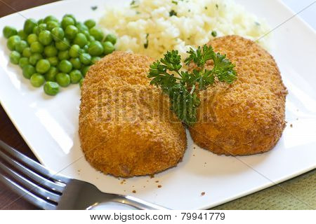 Breaded stuffed chicken cordon bleu with green peas white rice and parsley for garnish poster